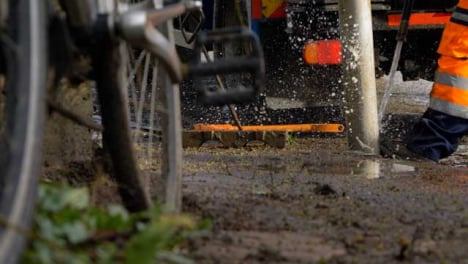 Low-Angle-Shot-of-Drainage-Workers-Using-High-Pressure-Hose-to-Clean-Blocked-Drain