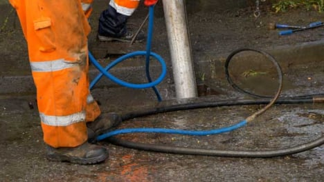 Handheld-Shot-of-Drainage-Workers-Feet-as-They-Attempt-to-Clear-Blocked-Drain