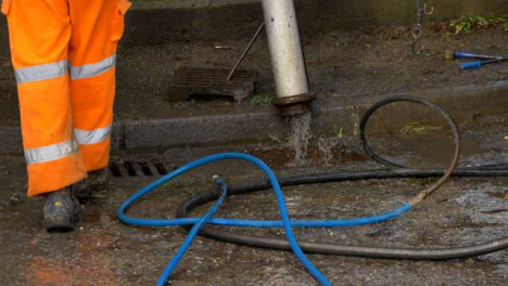 Handheld-Shot-of-Drainage-Workers-Feet-as-They-Retract-Pipe-Use-to-Clean-Blocked-Drain
