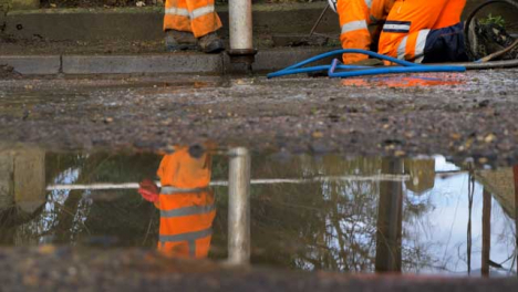 Low-Angle-Shot-of-Drainage-Worker-On-His-Knees-Attempting-to-Unblock-Drain