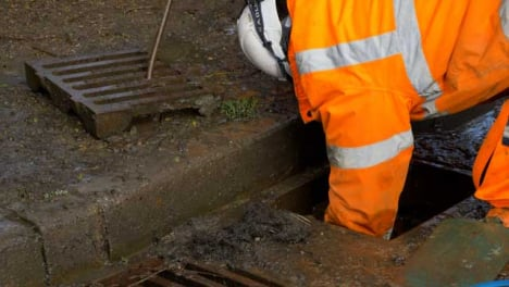 Handheld-Close-Up-Shot-of-Drainage-Worker-Attempting-to-Unblock-Drain