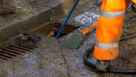 Handheld-Close-Up-Shot-of-Drainage-Workers-Attempting-to-Unblock-Drain-with-Hose