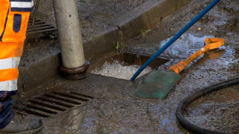 Handheld-Close-Up-Shot-of-Water-Bubbling-Up-as-Drainage-Workers-Attempt-to-Unblock-Drain
