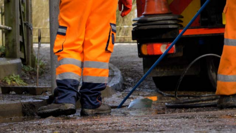 Low-Angle-Shot-of-Drainage-Workers-Feet-As-They-Work-to-Unblock-Drain