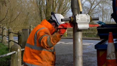 Handheld-Medium-Shot-of-Drainage-Worker-Holding-Suction-Pipe-Looking-Down-at-Blocked-Drain