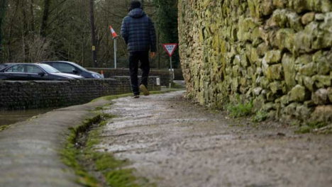 Low-Angle-Shot-of-Person-Walking-Along-Rural-Village-Path