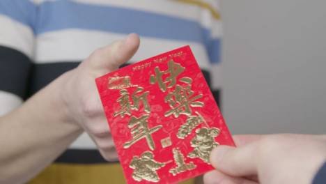 Close-Up-Shot-of-Hand-Giving-Chinese-New-Year-Red-Envelope-to-Person-