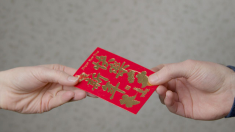 Close-Up-Shot-of-One-Hand-Taking-a-Red-Pocket-from-Another-On-Chinese-New-Year