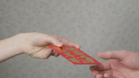 Close-Up-Shot-of-One-Hand-Taking-Red-Envelope-from-Another-On-Chinese-New-Year