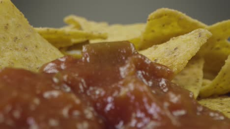 Sliding-Extreme-Close-Up-Shot-of-Nachos-Being-Dipped-Into-Sauce-