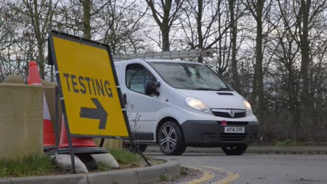 Close-Up-of-Cars-Driving-Past-COVID-19-Testing-Site-Road-Sign