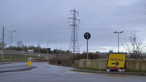 Wide-Shot-of-COVID-Testing-Site-Road-Sign-and-Background-Traffic-
