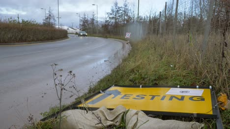 Wide-Shot-of-Car-Driving-Past-Fallen-Over-COVID-19-Test-Site-Road-Sign