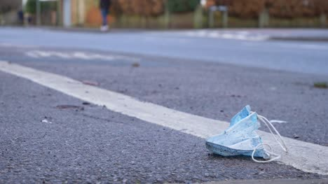 Close-Up-of-a-Discarded-Face-Mask-On-Floor-with-Cars-and-Pedestrians-In-Background