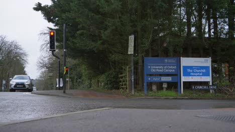 Wide-Shot-of-Ambulance-and-Other-Traffic-Passing-Churchill-Hospital-Sign