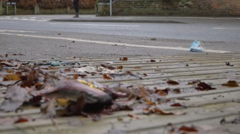 Low-Angle-Wide-Shot-of-Pedestrians-Walking-Past-Discarded-Face-Mask-On-the-Floor
