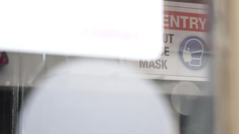 Handheld-Close-Up-Shot-of-COVID-19-Face-Mask-Sign-In-a-Shop-Window