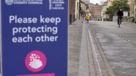 Handheld-Pull-Focus-Shot-of-COVID-Signage-with-People-Walking-In-Background