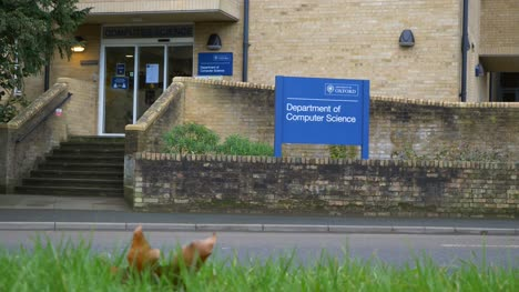 Low-Angle-Wide-Shot-of-Cars-Passing-University-of-Oxford-Computer-Science-Building-