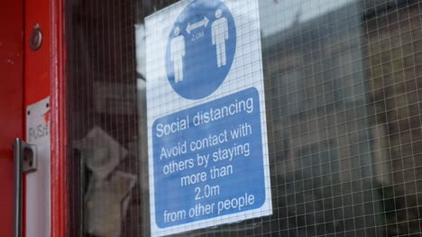 Handheld-Close-Up-of-Social-Distancing-Sign-In-Shop-Window