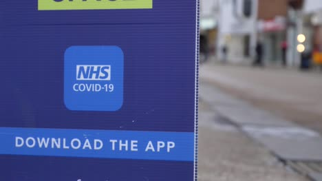 Handheld-Close-Up-Shot-of-COVID-NHS-Application-Signage-In-City-Centre