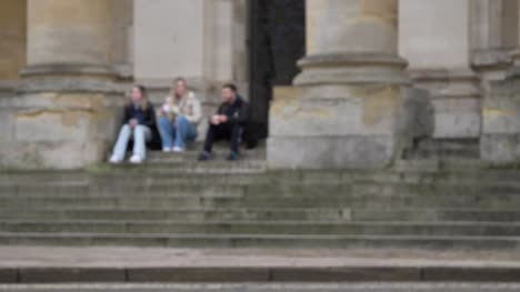 Defocused-Wide-Shot-of-People-Sitting-On-Steps-of-Clarendon-Building-as-Pedestrians-Walk-Past