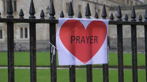 Handheld-Close-Up-Shot-of-A4-Prayer-Sign-Tied-to-Railing-