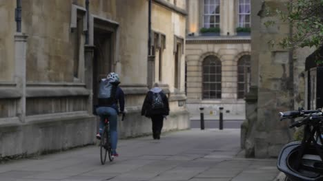 Handheld-Wide-Shot-of-Cyclist-and-Pedestrian-In-On-Catte-Street-In-Oxford
