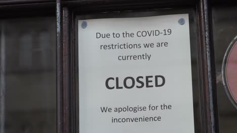 Handheld-Close-Up-Shot-of-Closure-Sign-In-Shop-Window-During-COVID-Pandemic