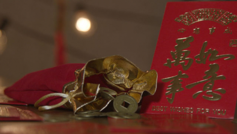 Sliding-Close-Up-Shot-of-Chinese-New-Year-Red-Pockets-and-Coins