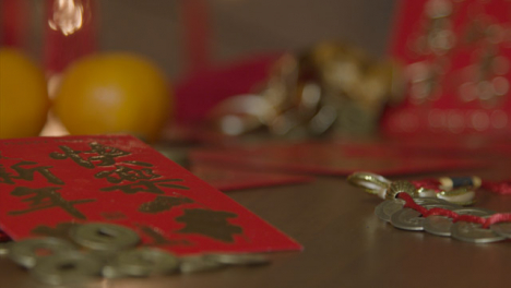 Sliding-Close-Up-Shot-of-Chinese-New-Year-Red-Packets-and-Coins