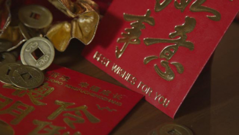 Sliding-Close-Up-Shot-of-Chinese-New-Year-Red-Envelopes-and-Coins
