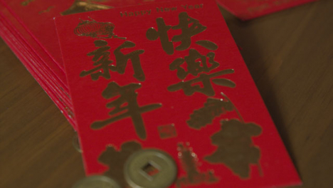 Sliding-Extreme-Close-Up-Shot-of-Chinese-New-Year-Red-Pockets-and-Coins