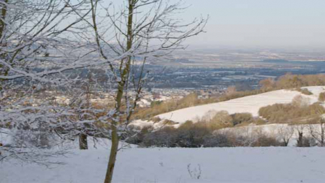 Panning-Shot-Overlooking-Snow-Covered-Hills-In-English-Cotswold-Countryside