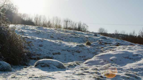 Panning-Close-Up-Shot-of-Countryside-Field-Covered-In-Snow
