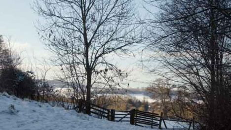 Tracking-Shot-Approaching-Fence-and-Gate-In-Snow-Covered-Countryside