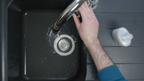 Top-Down-Shot-of-Male-Hands-Washing-Under-Running-Tap