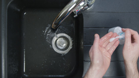 Top-Down-Shot-of-Male-Hands-Washing-Hands-with-Soap