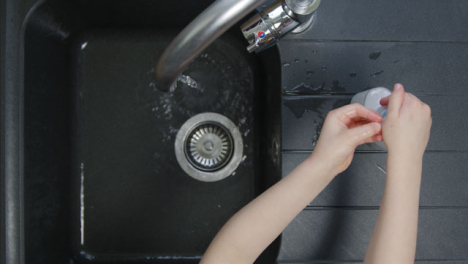 Top-Down-Shot-of-Young-Childs-Hands-Washing-with-Soap-Under-Kitchen-Tap