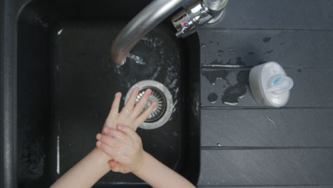Top-Down-Shot-of-Young-Childs-Hands-Washing-Under-Tao-Before-Turning-It-Off
