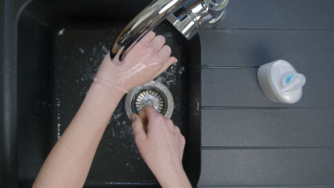 Top-Down-Shot-of-Female-Hands-Washing-Under-Running-Tap-with-Soap