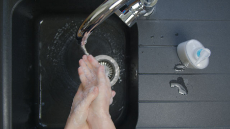 Top-Down-Shot-of-Female-Hands-Rinsing-Soap-from-Hands-Under-Running-Tap