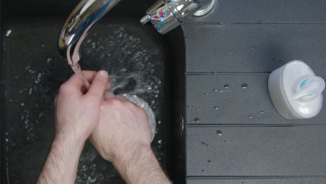 Top-Down-Shot-of-Male-Hands-Turning-On-Tap-and-Washing-Hands
