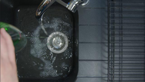 Top-Down-Shot-of-Male-Hands-Pouring-Washing-Liquid-into-Sink-Under-Running-Tap