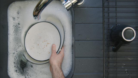 Top-Down-Shot-of-Male-Hands-Placing-Dirty-Dishes-into-Sink-of-Soapy-Water
