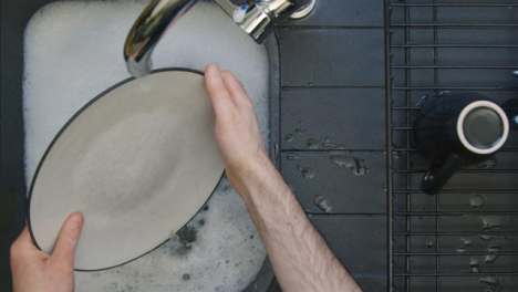 Top-Down-Shot-of-Male-Hands-Washing-Plate-In-a-Sink-of-Soapy-Water