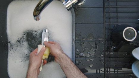Top-Down-Shot-of-Male-Hands-Washing-Knives-In-Sink-of-Soapy-Water