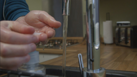 Medium-Shot-of-Male-Hands-Turning-On-Kitchen-Tap-and-Washing-Under-Running-Water