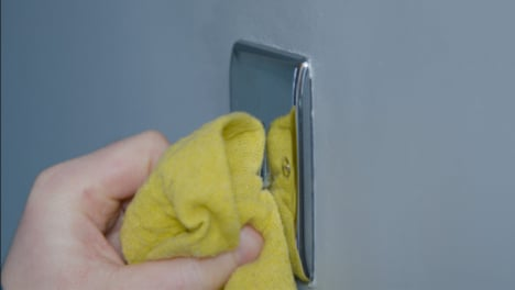 Close-Up-Shot-of-Male-Hand-Cleaning-a-Light-Switch-On-Wall