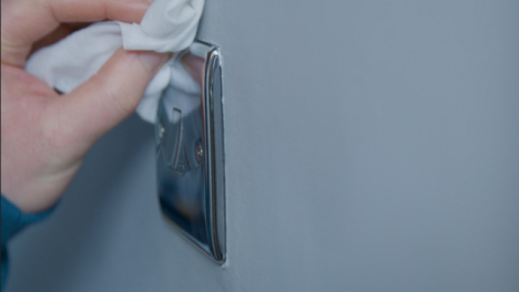 Sliding-Close-Up-Shot-of-Male-Hand-Cleaning-Light-Switch-On-Wall